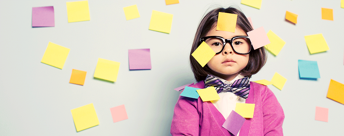 Little Asian girl wearing glasses surrounded by post-it notes of various colors