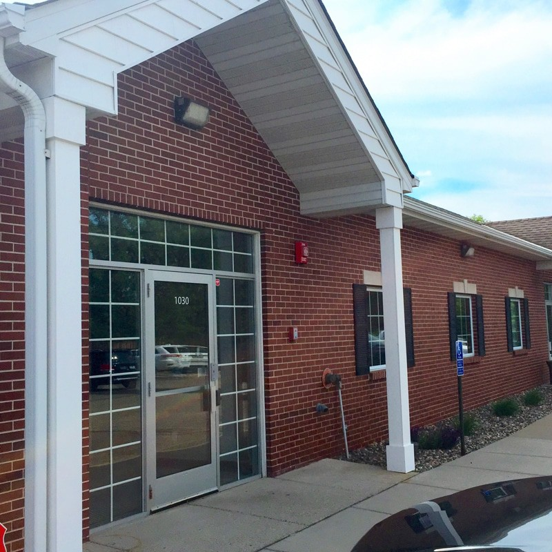 A picture of a red brick building with a glass front door. The front entrance of Lake Area Mortgage.