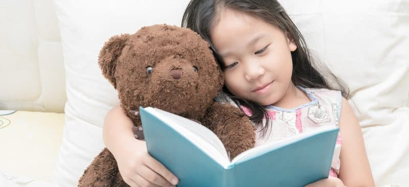 child with bear and book