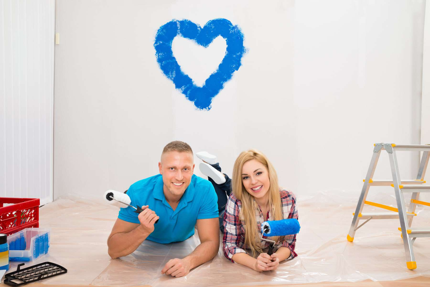 young couple painting heart on wall